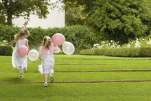 Rear View Of Little Bridesmaids With Balloons Running In Garden