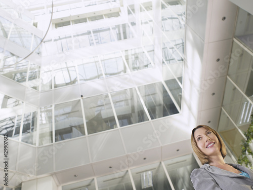 Low angle view of a smiling businesswoman standing in atrium of office building Wallpaper Mural