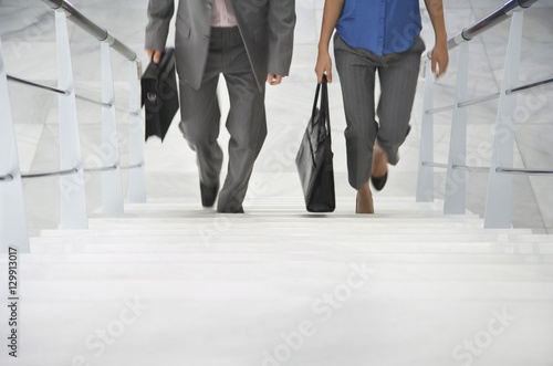Foto  Lowsection of two businesspeople walking up stairs with bags in office