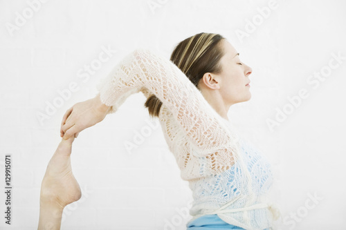Fotografie, Obraz  Side view of woman practicing one-legged king pigeon pose on white background