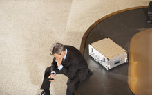 Elevated View Of A Businessman Looking At Mobile Phone While Sitting By Luggage On Carousel In Airport