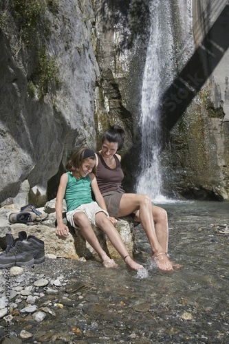 Fototapety, obrazy: Full length of a mother and daughter sitting on rock by waterfall
