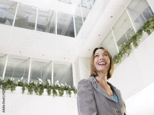 Photo Smiling businesswoman standing in atrium of office building low angle view