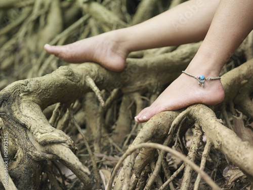 Closeup of a young woman's bare feet on roots Wallpaper Mural