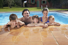 Portrait Of A Happy Couple With Three Children In Swimming Pool