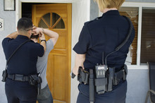 Rear View Of Police Officers Arresting Young Man Outside House