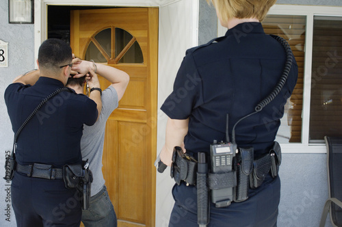 Canvas Print Rear view of police officers arresting young man outside house