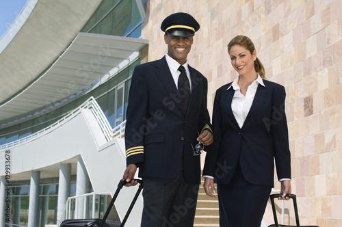 Portrait of happy pilot and flight attendant outside building Wallpaper Mural