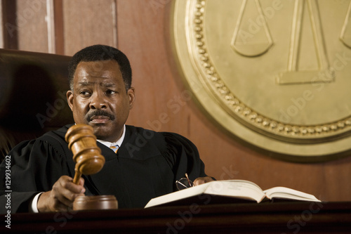 Fotografie, Obraz Serious middle aged judge knocking a gavel