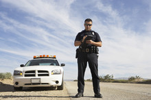 Full Length Of A Police Officer Writing On Clipboard While Standing In Front Of Patrol Car
