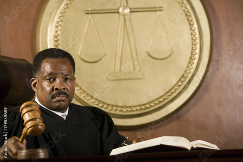 Fototapeta Portrait of a male judge holding wooden gavel in courtroom