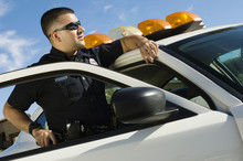 Male Police Officer With Gun Leaning On Patrol Car