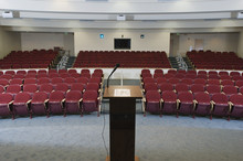 Red Chairs Arranged In Order And Podium At An Empty Conference Auditorium