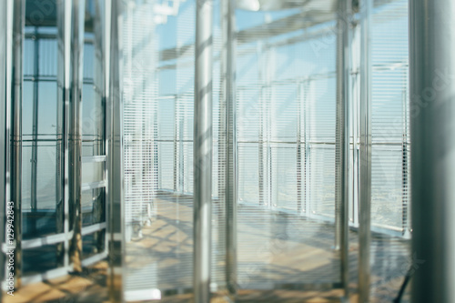 Abstract office interior background, the sun rays, glass, steel columns and blinds, view from skyscraper through the window, the Dubai cityscape outside