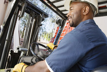 Happy African American Industrial Worker Driving Forklift At Workplace