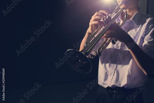 Slika na platnu young trumpet player in dark