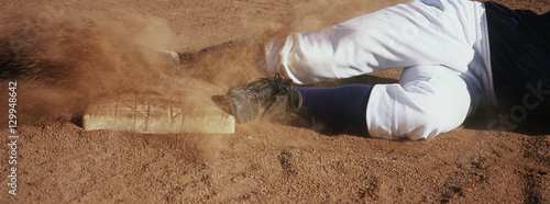 Photo  Low section of baseball player sliding towards base on field