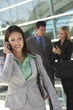 Beautiful businesswoman using cell phone with colleagues in background