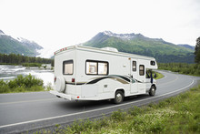 Recreational Vehicle Passing Through A Lakeside Road With Mountain In Background, Alaska, USA