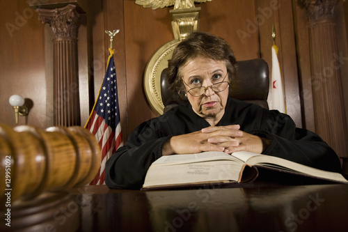 Fotografering  Portrait of female judge with law book in the courtroom