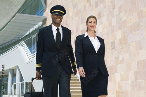 Photo Portrait of happy pilot and flight attendant walking outside building