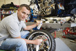 Portrait of a male mechanic working on a tire at workplace