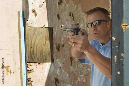 Fototapety, obrazy: Caucasian man aiming handgun at firing range during weapons training