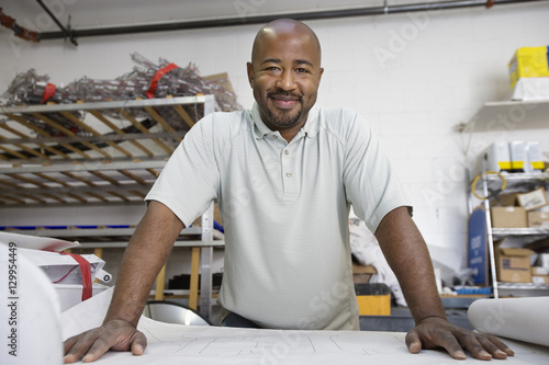 Photo  Portrait of happy African American male architect with blueprint at workplace