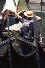 Gondolier Relaxing In Gondola, Venice, Veneto