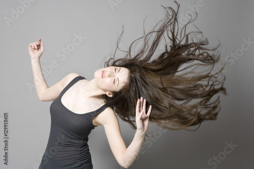 Leinwand Poster Young woman with long brown wavy hair dancing against gray background