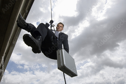 Low angle view of a spy rappelling with suitcase against cloudy sky Wallpaper Mural