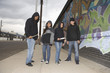 Portrait of four young multiethnic people with knives on sidewalk