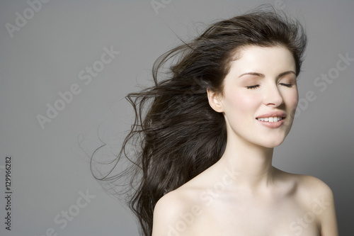 Valokuva  Closeup of a beautiful woman with long brown hair and eyes closed against gray b