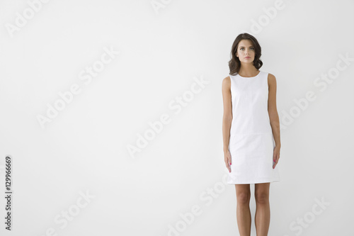 Fotografija  Portrait of a serious young woman in white dress against white background