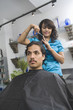 Young female hairdresser cutting man's hair at salon