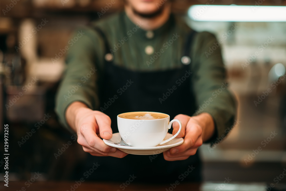 Fototapeta Waiter in black apron stretches a cup of coffee