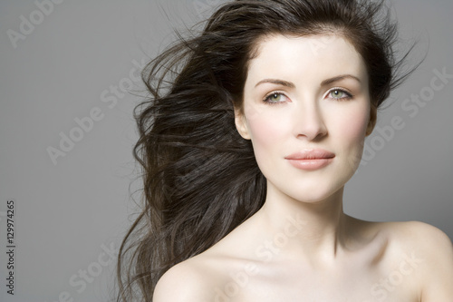 Fényképezés  Closeup portrait of a beautiful woman with long hair against gray background