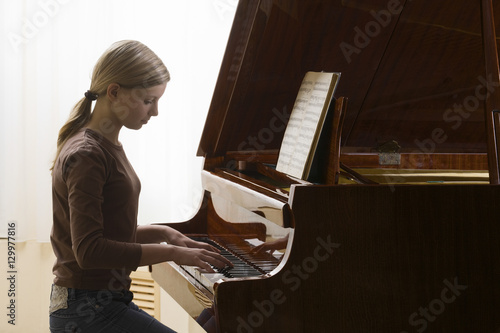 Fotografie, Obraz  Side view of a teenage girl playing the piano