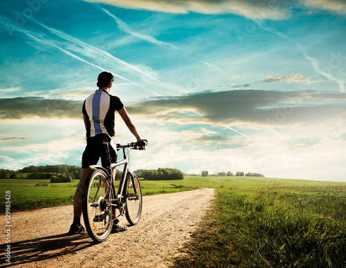 Foto auf Leinwand Radsport Rear View of a Young Man With Bicycle on Summer Nature Background. Healthy Lifestyle and Mountain Bike Cycling Concept. Toned Photo with Copy Space.