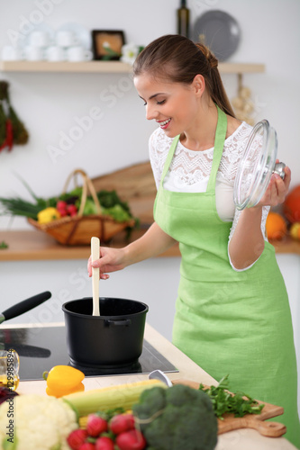 Papiers peints Cuisine Young woman in the green apron cooking in the kitchen. Housewife is preparing the soup