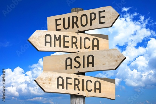 Fotografie, Tablou  Wooden signpost with four arrows - Europe, America, Asia, Africa - great for topics like continents, traveling etc