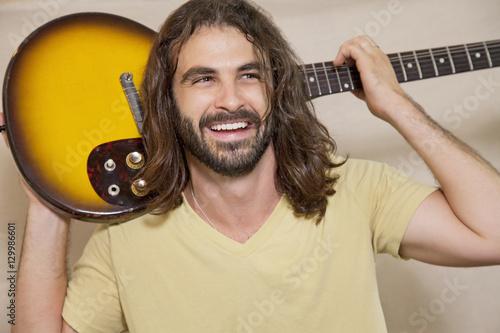 Spoed Foto op Canvas Muziekwinkel Happy man holding guitar on back of his shoulders