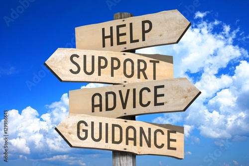 Photo Wooden signpost with four arrows - help, support, advice, guidance - great for topics like frequently asked questions, customer support etc