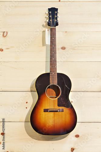 Spoed Foto op Canvas Muziekwinkel Acoustic guitar with label isolated on a wood grain wall