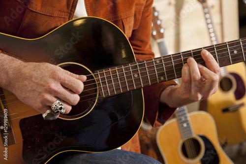 Spoed Foto op Canvas Muziekwinkel Close-up of man's torso practicing with guitar