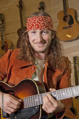 Spoed Foto op Canvas Muziekwinkel Portrait of handsome man playing guitar