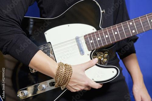 Spoed Foto op Canvas Muziekwinkel Midsection of young woman holding electric guitar
