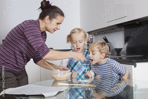 Valokuva  Mother with children baking and tasting cookie batter in kitchen