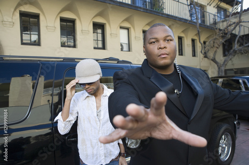 Photo  Male celebrity with his bodyguard against a vehicle
