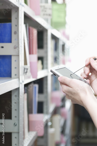 Photo  Closeup of woman's hands using PDA in library